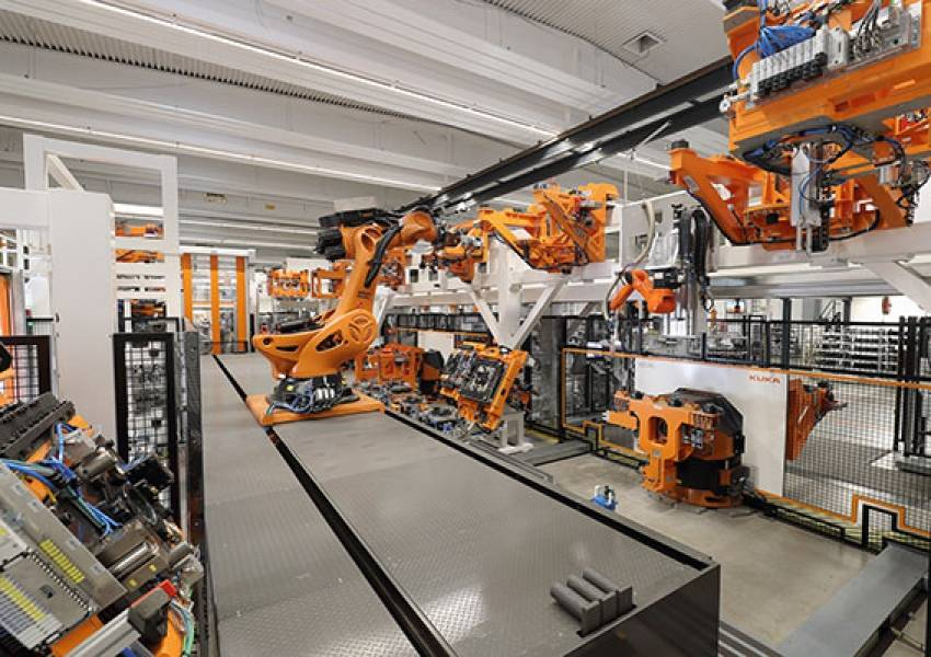 Station 1: The KUKA Titan removes a base frame from the clamping device